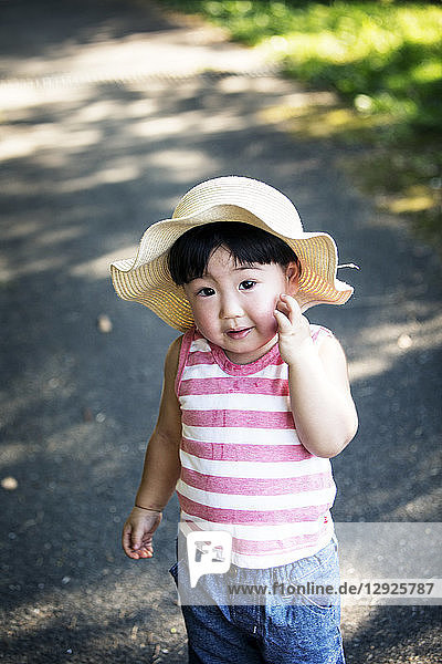 Two Japanese girls wearing sun hats standing on path  holding hands.