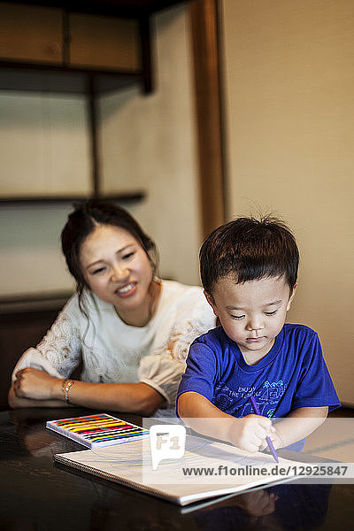 Smiling Japanese woman and little boy sitting at a table  drawing on white paper with colouring pens.