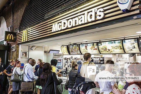 United Kingdom Great Britain England  London  South Bank  Waterloo Station  McDonald's  fast food  restaurant  counter  line  queue  ordering  Black  man  woman