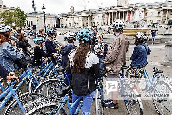 United Kingdom Great Britain England  London  Trafalgar Square  guided bicycle  helmets  man  woman  girl  standing  listening
