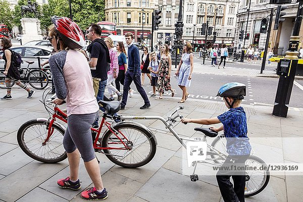 United Kingdom Great Britain England  London  St. Saint James's  Trafalgar Square  sidewalk  walking  Trailgator  bicycle trailer  cyclist  woman  boy  mother  son  helmet  pedestrians