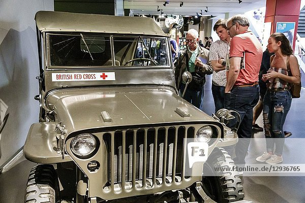 United Kingdom Great Britain England  London  Southwark  Imperial War Museum  military war weapons archives  inside  interior  exhibit  British Red Cross  jeep  Willys MB Jeep 4x4  Second World War  man  woman  looking