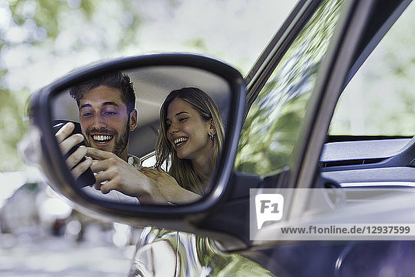Smiling couple using smartphone