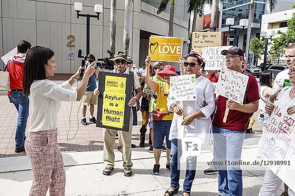Florida,  Miami,  demonstration demonstrating protest protesting,  Families Belong Together Free Children illegal immigration,  social media,  Mexican border family separations,  woman,  man,  Hispanic,  interviewing,  smartphone video camera,  holding signs posters