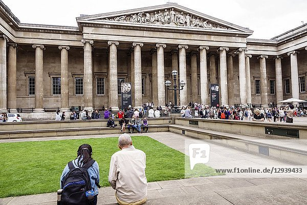 United Kingdom Great Britain England  London  Bloomsbury  The British Museum  human culture history  exterior  courtyard  facade  front entrance  ionic column  pediment  neo-classical architecture  Greek Revival  Sir Robert Smirke  man  woman  sitting  crowd