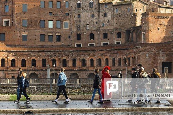Roman soldier takes on the tourists opposite Trajan's Market on on the Via dei Fori Imperiali Road. Rome. Italy.