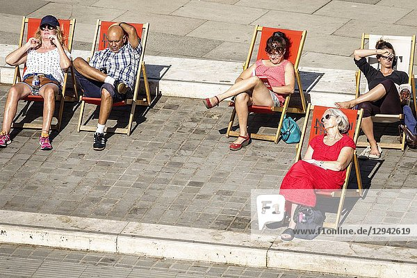 United Kingdom Great Britain England  London  Lambeth South Bank  National Theatre theater plaza  deck chairs  basking  man  woman  leisure