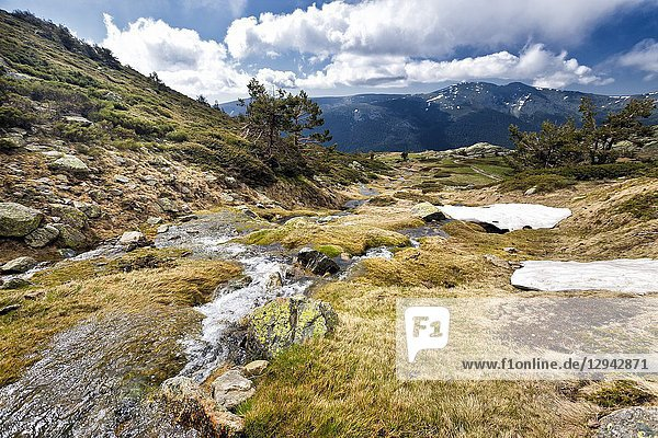 Thaw at National Park of Penialara Lagoons and Iron Heads peaks on the background. Sierra de Guadarrama. Madrid. Spain.