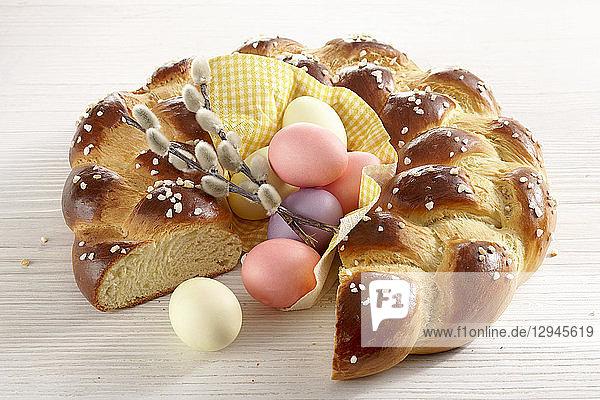 Hefekranz zum Osterfrühstück mit bunten Ostereiern und Palmkätzchen