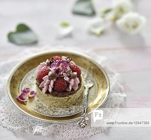 Veganes Zucchini-Küchlein mit Schokoganache  Himbeermousse  frischen Himbeeren  Schokoröllchen und getrockneten Rosenblütenblättern
