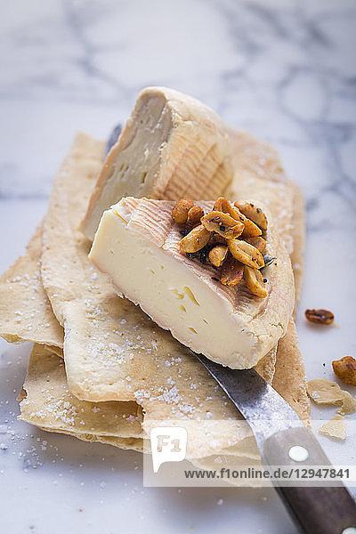 Zwei Stücke Munsterkäse mit Erdnüssen auf dünnem Fladenbrot