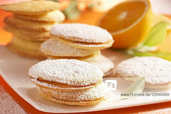 Orangenplätzchen mit Marmeladenfüllung und Puderzucker