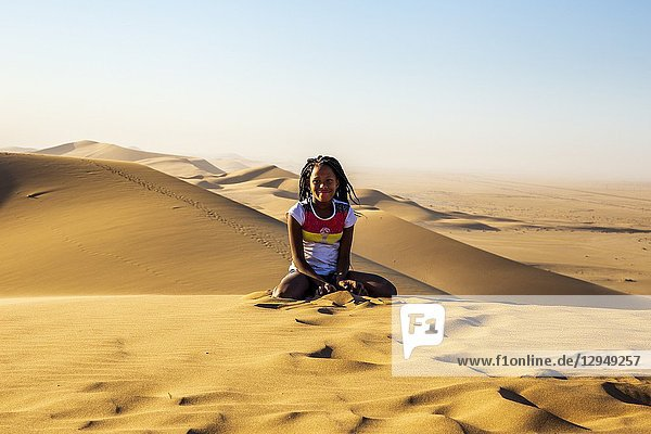 Young girl posing for a portrait on top of a sand dune Walvis Bay Namibia Africa.