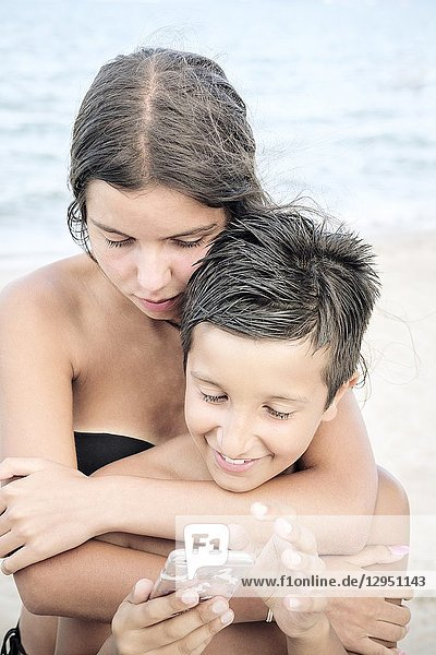 Brother and sister watching video on smart phone on the beach.