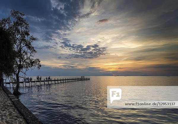 Tourists view sunset by pier in kep town on cambodia coast.