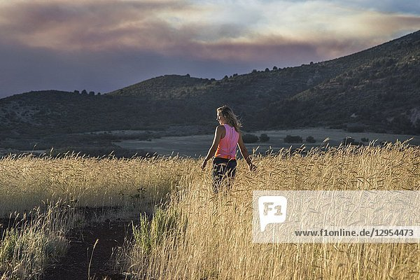 A woman appears in a field in Southern Utah at sunset.