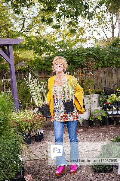 A pretty 42 year old blond woman shopping at a garden store carrying 2 potted iris ensata plants.