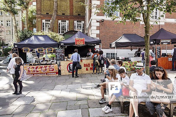United Kingdom Great Britain England  London  West End St James's Piccadilly Church  St James-in-the-Fields  Anglican Church parish  exterior  Market  food vendor stall  man  woman  boy  girl  sitting