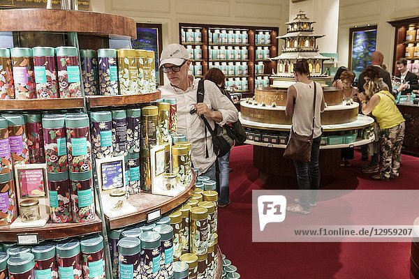 United Kingdom Great Britain England  London  West End St James's  Piccadilly  Fortnum & Mason  shopping  inside interior  luxury upmarket department store groceries  exotic teas  biscuit tins  man  woman  display sale