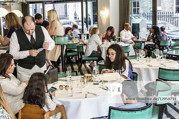 United Kingdom Great Britain England  London  Mayfair  Cecconi's  restaurant  Italian cuisine  dining  Middle Eastern woman  boy  girl  teen  man  family waiter  writing order  tables  patrons  busy