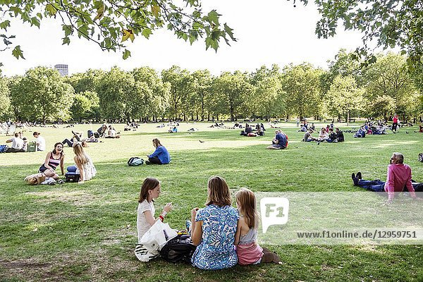 United Kingdom Great Britain England  London  Green Park  Ritz Corner  Royal Parks  lawn  outdoors  green space  sitting on grass  woman  girl  family  man  shade