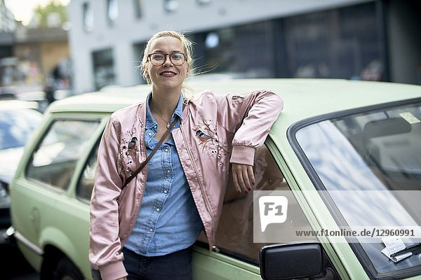 Portrait of woman leaning against vintage car in Berlin  Germany
