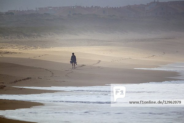 A person walking on the beach  Supertubos beach  Peniche  Portugal. Every year the best 40 surfers in the world come to Peniche to surf this wonderful wave. Supertubo is included in the ASP World Tour.