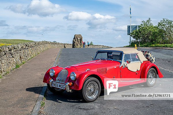 A red Morgan Roadster convertible rests parked on the side of the road near the Anglo-Scottish border at Carter Bar  Scotland.
