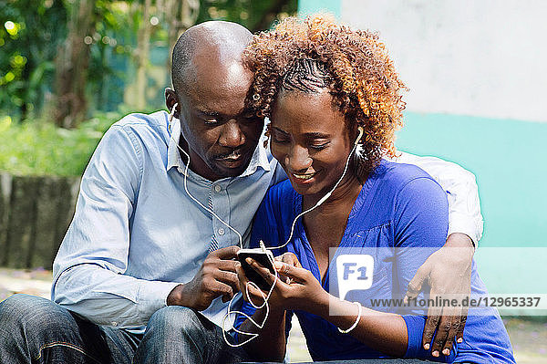 This happy couple sitting in a park and share a common telephone information.