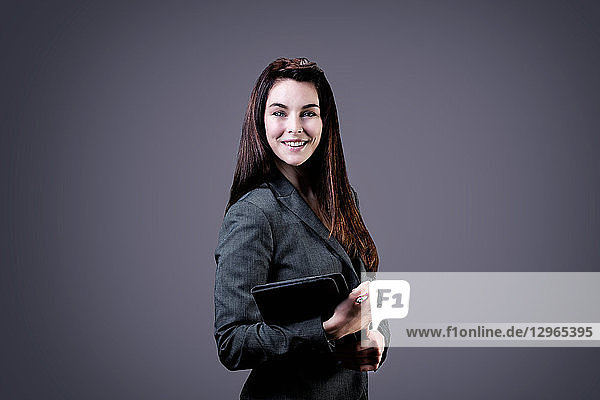Portrait of a smiling young businesswoman  a touch pad in her hands