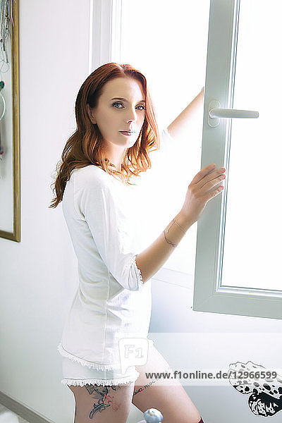 Young smiling woman opening the window of her room