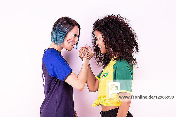Arm wrestling of two young fans of the Brazil team and the France team
