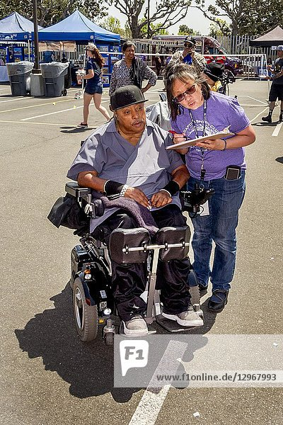 At an Adaptive Sports Expo in Long Beach  CA  a Hispanic volunteer counsels a wheelchair-bound African American man on activity options for the handicapped.