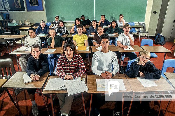 A stoical group of multiracial high school students pose in a classroom in Riverside  CA.