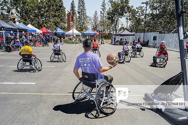 Multiracial handicapped members of a wheelchair basketball team play a game at an Adaptive Sports Expo in a Long Beach  CA  parking lot. Note exhibitors canopies.