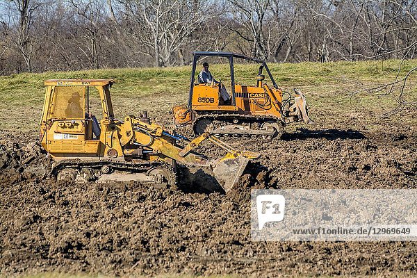 Bulldozer and scoop equipment spreading dirt in a sinkhole in Kentucky USA.