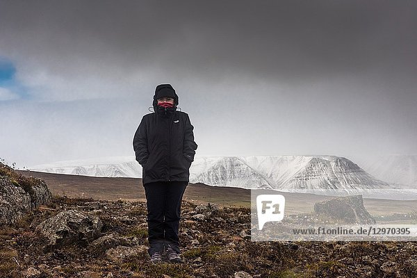 Woman with cold on the outskirts of Akureyri. North Region. Iceland.