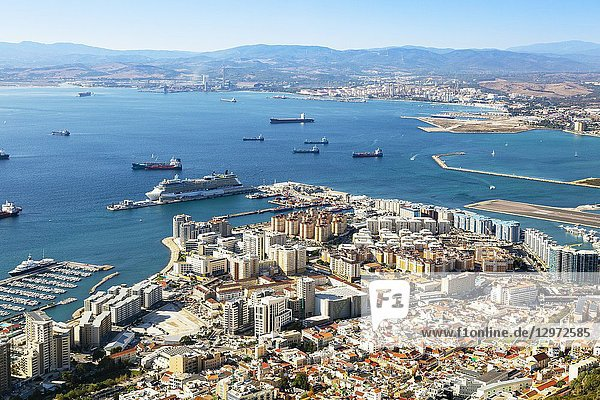 High view over Gibraltar harbour with a cruise liner berthed at Western Arm of Container Quay  and a view over the Bay of Gibraltar to the Spanish mainland.