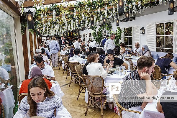 United Kingdom Great Britain England  London  Marylebone  Selfridges Department Store  shopping  inside interior  upmarket  luxury retail  alto by San Carlo  alfresco dining  roof restaurant  man  woman  young adults  waiter  pergola arbor  crowded busy