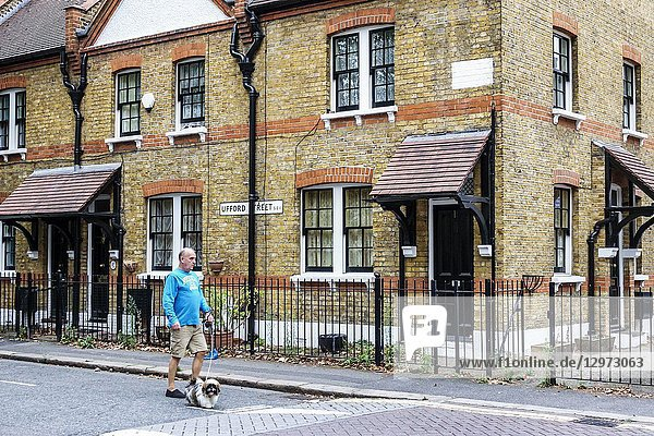United Kingdom Great Britain England  London  Lambeth South Bank  Ufford Street Conservation Area  terraced houses  exterior outside  residential area  brick  resident  man  walking  dog  pet  leash