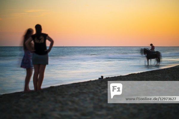 Two women contemplating a horseman on the beach at sunset  Ayamonte  Spain.