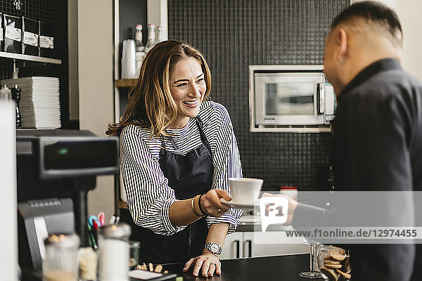 Barista serving coffee to customer in cafe