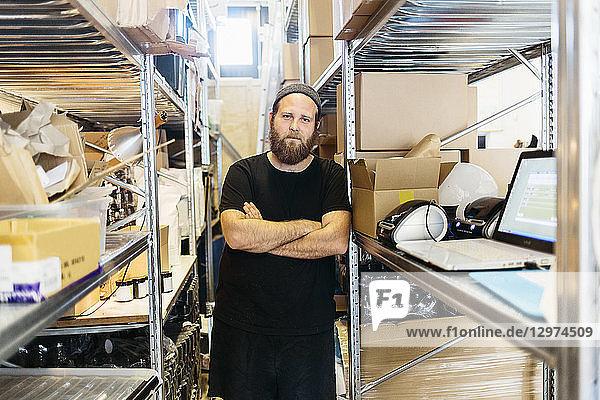 A coffee roaster posing between shelves in Sweden