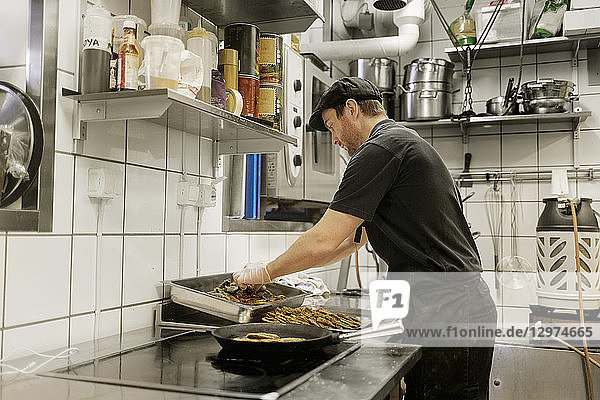 Fishmonger cooking in kitchen