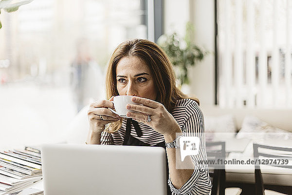 Barista drinking coffee by laptop in cafe