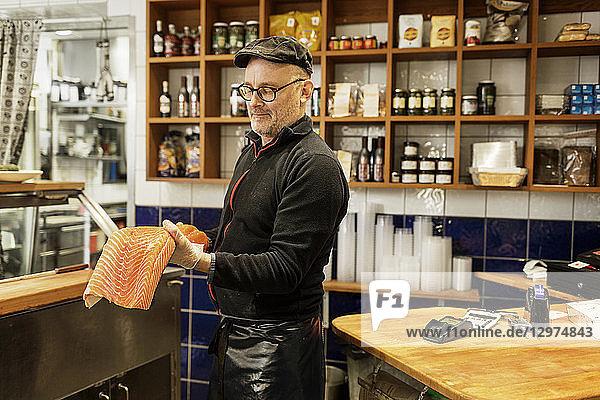 Fishmonger holding salmon in store