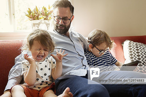 Crying girl and family sitting in a living room in Sweden