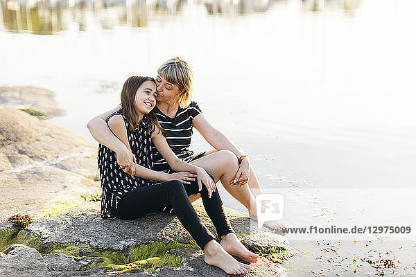 Mother and daughter sitting by the sea at sunset in Blekinge  Sweden