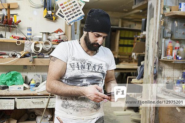 Carpenter holding a cellphone in Sweden