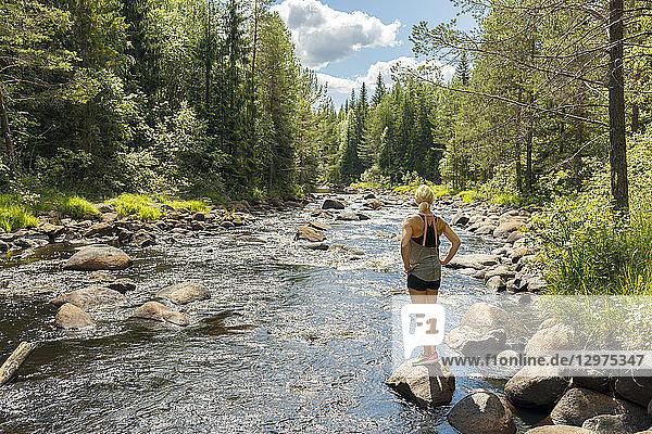 Woman on riverbank in Syssleback  Sweden